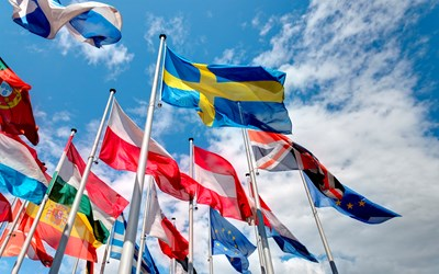 International flags against a blue sky with white clouds