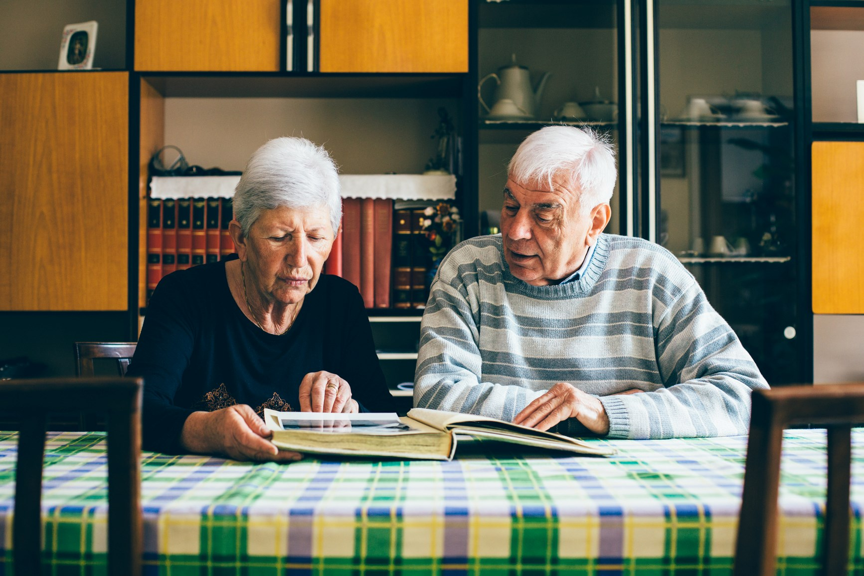 Older couple sat at table looking through photo album