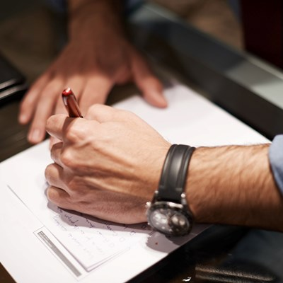 Hand holding a pen writing notes