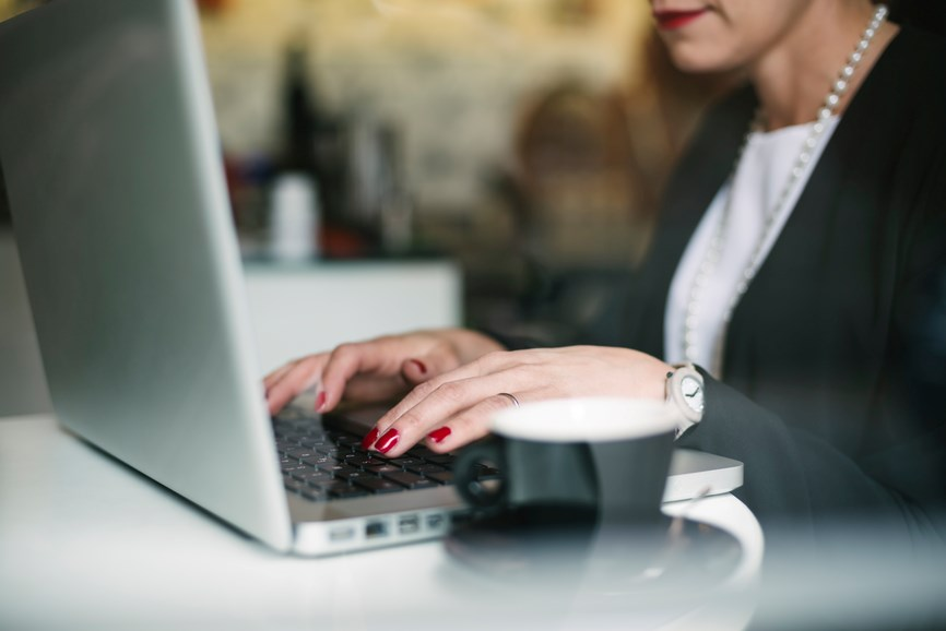 Close up view of woman's hand typing on a laptop with a coffee cup