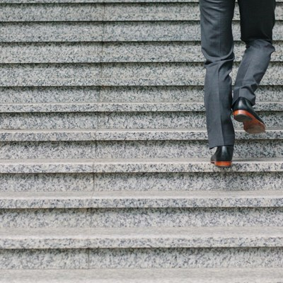 Grey steps with a pair of legs climbing up