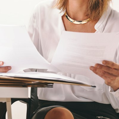 Close up of woman looking at papers on desk