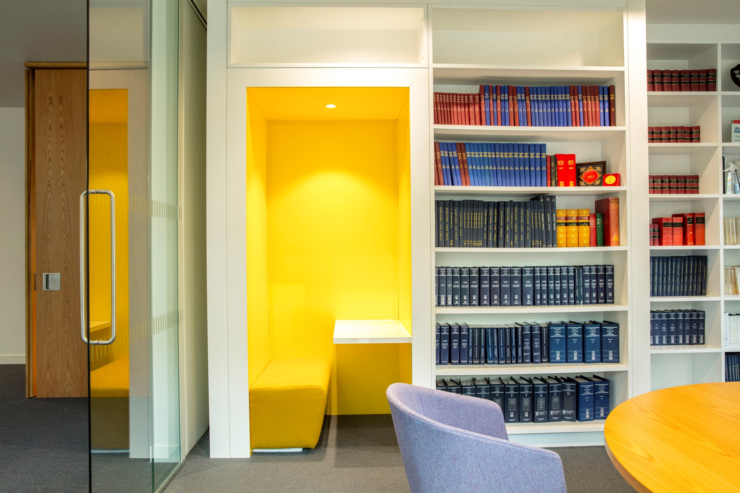A meeting room with yellow booth and library books