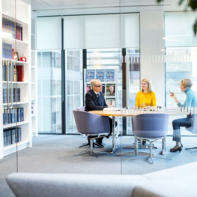 View of three people in a meeting room from a distance