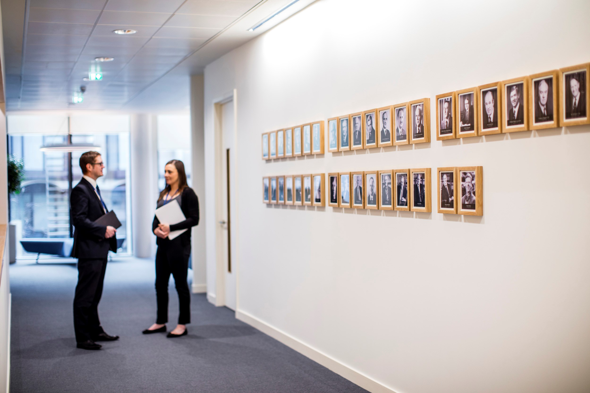 A corridor lined with photographs and two people standing and chatting