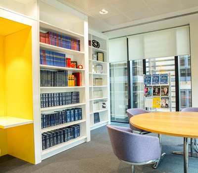 A meeting room with yellow booth, library books and a round table
