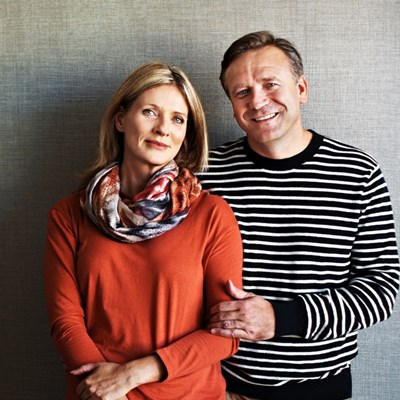 A woman in an orange jumper and a man in a stripey black and white jumper