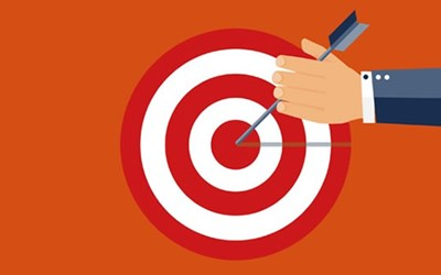 Orange background with target illustration and hand holding arrow in the bullseye