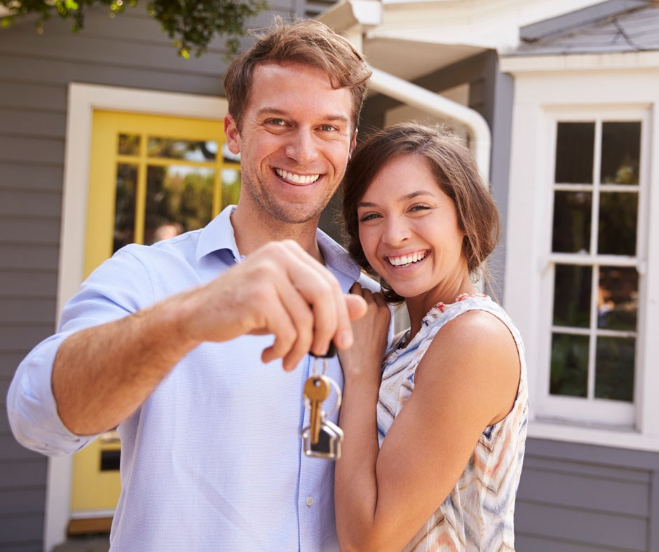 A couple holding keys in front of a house