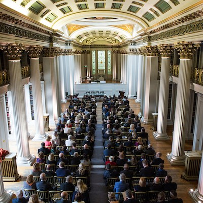Ariel view of people seated in a grand room