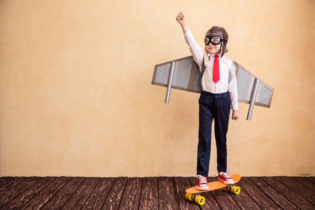 A boy on a skateboard with cardboard wings and flight hat and goggles